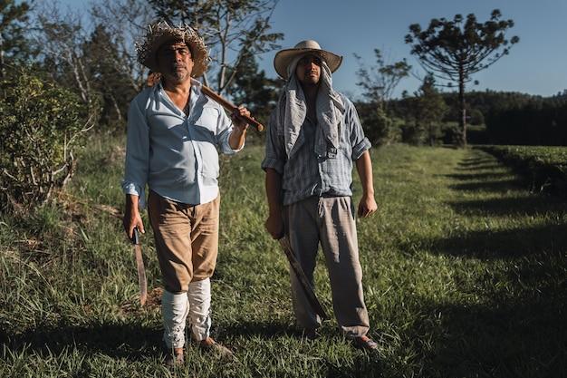 Portret van volwassen mannen die met een schoffel op het land werken.