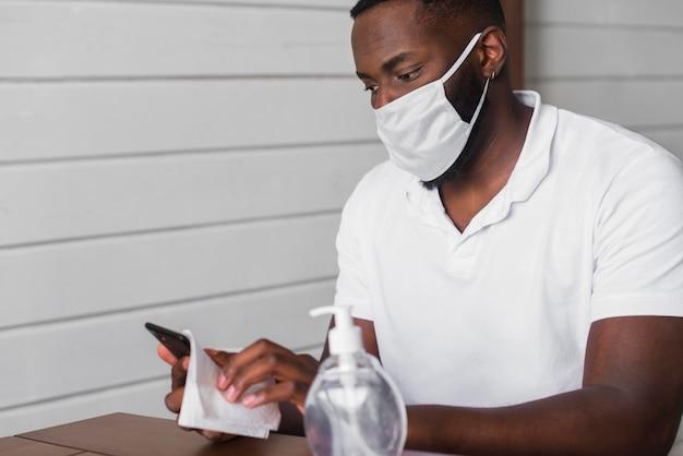 Portret van volwassen mannetje dat mobiele telefoon desinfecteert