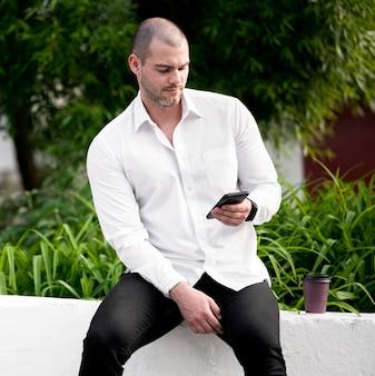 Portret van volwassen mannetje dat mobiele telefoon doorbladert