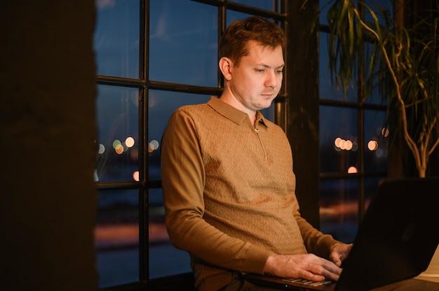 Portret van volwassen mannetje dat op laptop werkt
