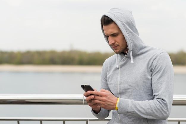 Portret van volwassen mannetje dat zijn mobiele telefoon controleert