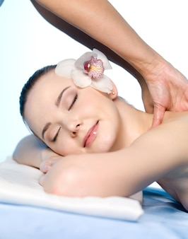 Portret van volwassen meisje met massage en plezier op haar schouders - close-up