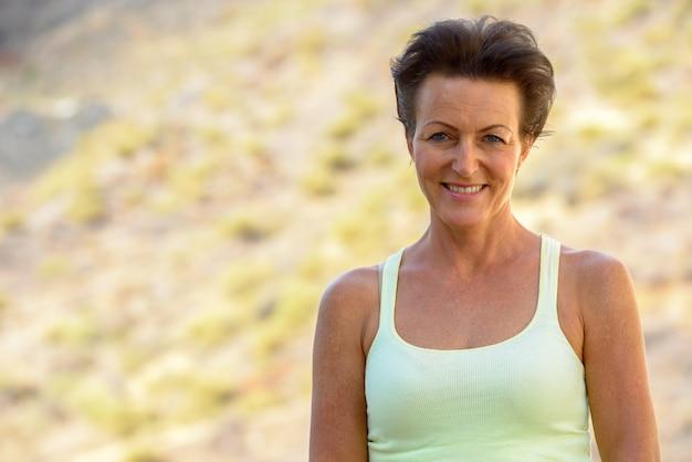 Portret van volwassen mooie toeristische vrouw met natuur buiten