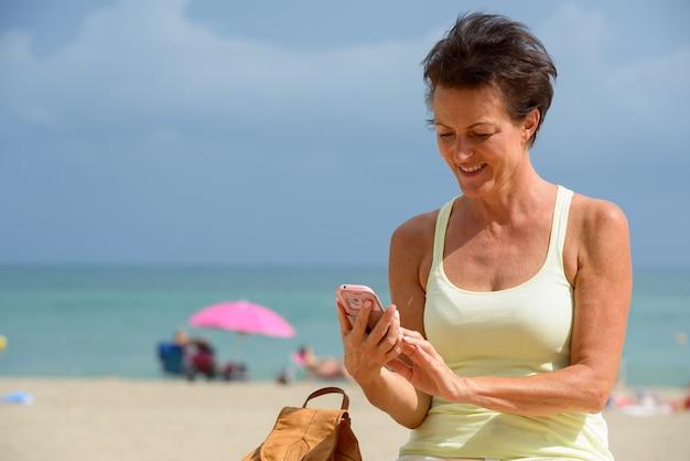 Portret van volwassen mooie toeristische vrouw op het strand buiten