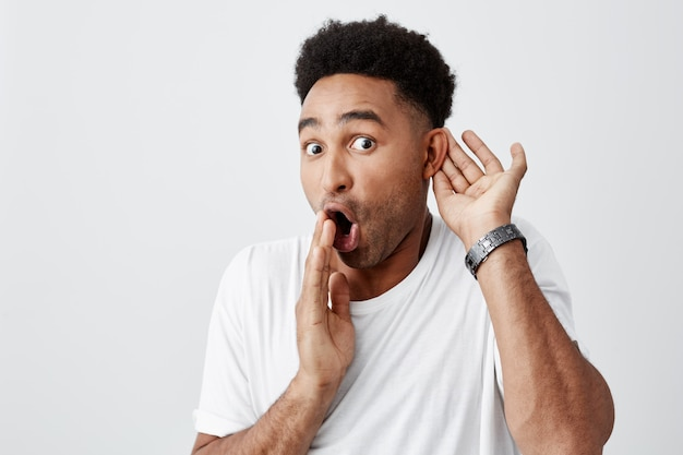 Portret van volwassen mooie zwarte huid geschokt man met afro kapsel in casual wit t-shirt met de hand in de buurt van de mond, roddel luisteren over zijn baas met verbaasde uitdrukking