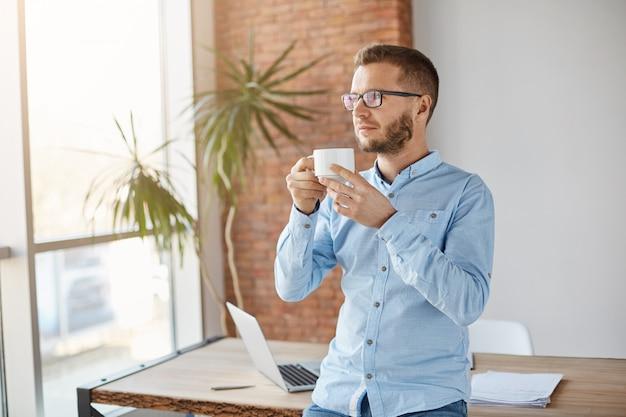Portret van volwassen ongeschoren blanke zakenman in glazen en klassieke shirt staan in lichte kantoor, koffie drinken, ontspannen tijdens de pauze. bedrijfsconcept.