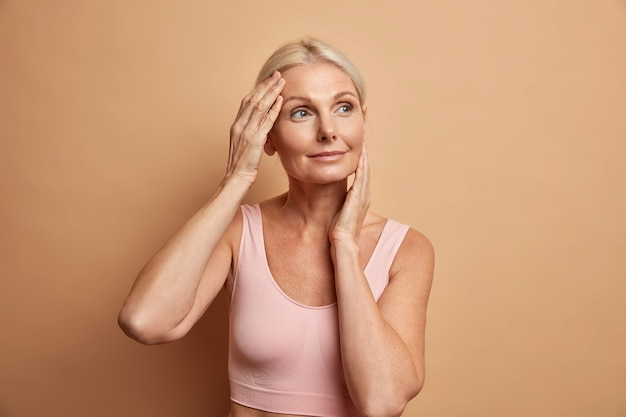 Portret van volwassen oudere europese vrouw raakt gezicht zachtjes heeft perfecte huid en kijkt bedachtzaam weg geniet van haar zachte teint geeft om uiterlijk tevreden na anti-verouderingsprocedure
