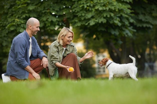 Portret van volwassen paar spelen met hond in park, focus op lachende vrouw met bal naar jack russel terrier