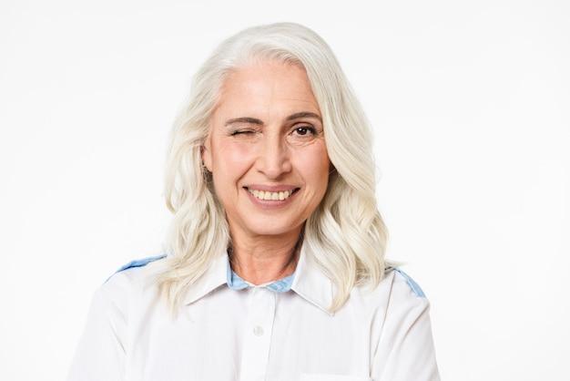 Portret van volwassen prachtige vrouw met grijze haren knipogen en lachend met perfecte tanden, geïsoleerd over witte muur