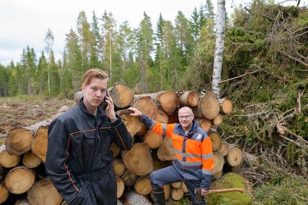 Portret van volwassen scandinavische man en jonge scandinavische man klaar om samen buiten in het bos te oogsten