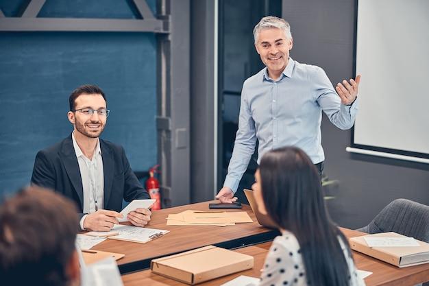 Portret van volwassen senior projectmanager die op kantoor gebaren maakt