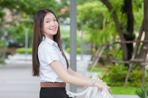 Portret van volwassen thaise student in universitair studentenuniform. aziatisch mooi meisje zit gelukkig glimlachend aan de universiteit in de buitenlucht met een achtergrond van tuinbomen.
