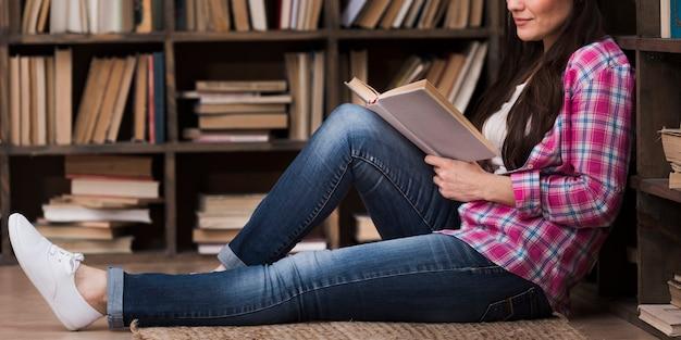 Portret van volwassen vrouw die een boek leest
