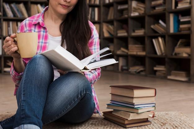 Portret van volwassen vrouw die een roman leest