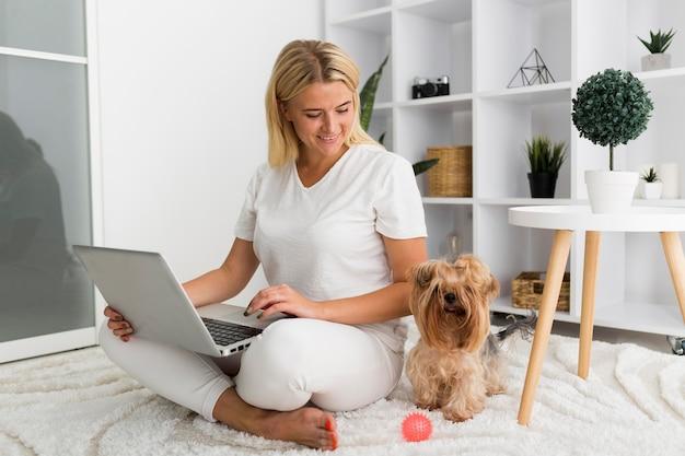 Portret van volwassen vrouw die geniet van het werken met huisdier