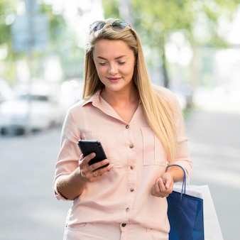 Portret van volwassen vrouw die mobiele telefoon doorbladert