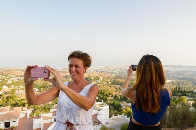 Portret van volwassen vrouw en jonge aziatische vrouw als toeristen samen in mijas dorp malaga spanje costa del sol