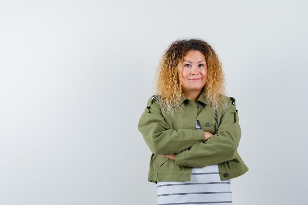 Portret van volwassen vrouw met armen gekruist in groene jas, t-shirt en op zoek vrolijk vooraanzicht