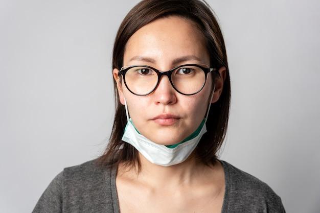 Portret van volwassen vrouw met chirurgisch masker