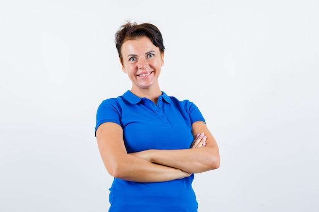 Portret van volwassen vrouw permanent met gekruiste armen in blauw t-shirt en op zoek naar vertrouwen vooraanzicht