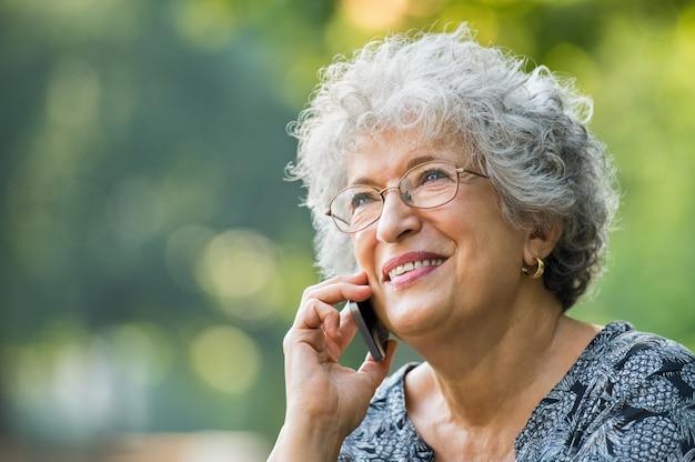 Portret van volwassen vrouw praten over smartphone buiten