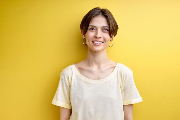 Portret van volwassen vrouw schattig glimlachend poseren op camera geïsoleerd over gele achtergrond gekleed casual...