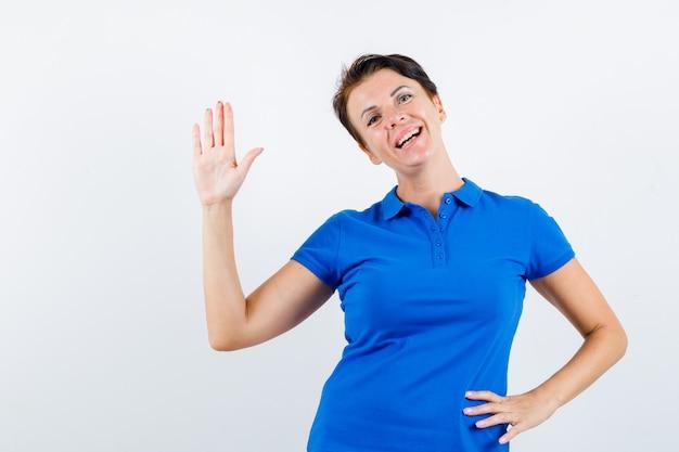 Portret van volwassen vrouw zwaaiende hand om afscheid te nemen in blauw t-shirt en op zoek blij vooraanzicht