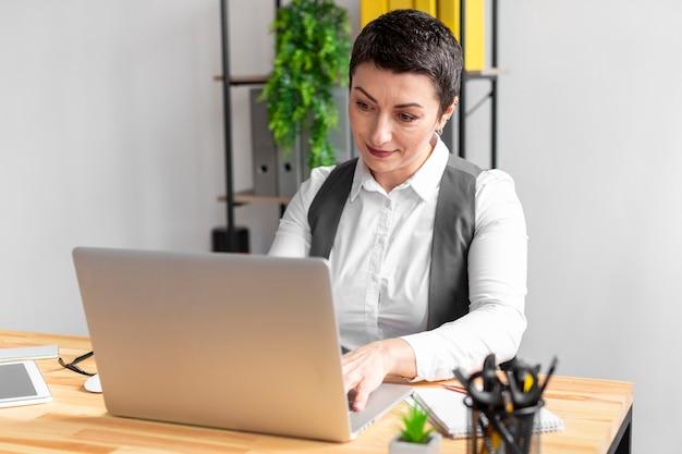 Portret van volwassen vrouwtje die op laptop werkt