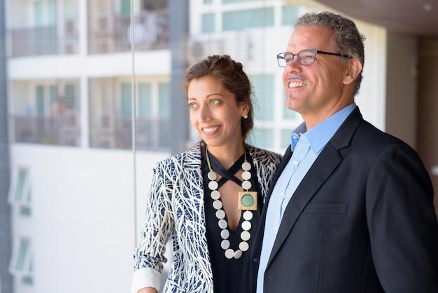 Portret van volwassen zakenman en mooie onderneemster samen