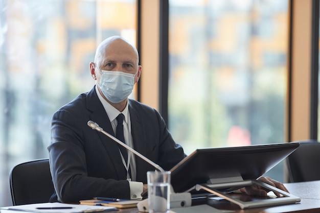 Portret van volwassen zakenman in beschermend masker zit achter de computer en kantoor kijken