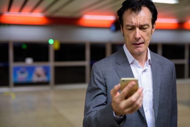 Portret van volwassen zakenman met behulp van telefoon in treinstation