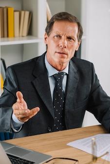 Portret van volwassen zakenman op werkplek gebaren