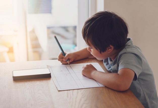Portret van voorschoolse jongen met behulp van mobiele telefoon voor zijn huiswerk