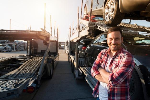 Portret van vrachtwagenchauffeur met gekruiste armen auto's naar de markt vervoeren.