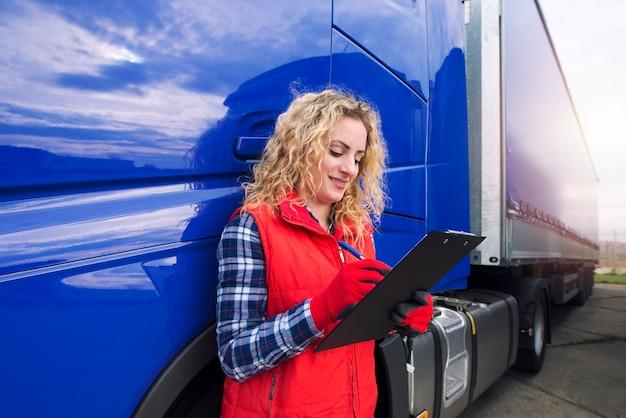 Portret van vrachtwagenchauffeur papierwerk doen door vrachtwagen voertuig.