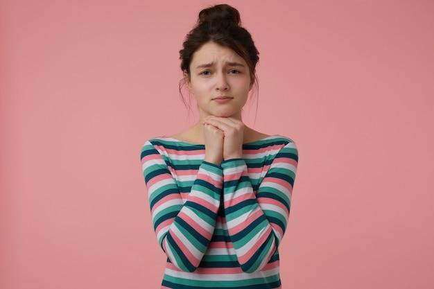 Portret van vragend, droevig uitziend meisje met donkerbruin haar en knot. het dragen van gestreepte blouse en hand in hand onder haar kin. emotioneel begrip. geïsoleerd over pastelroze muur