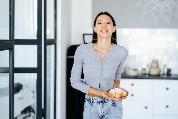 Portret van vreugde vrouw eet lekkere croissant thuis. ongezonde voeding concept.