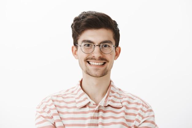 Portret van vriendelijk ogende gelukkig aantrekkelijk mannelijk model met snor en baard, trendy transparante bril, breed glimlachend terwijl u luistert naar een interessant verhaal of wacht tot moeder een maaltijd geeft