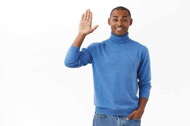 Portret van vriendelijke charismatische jonge afro-amerikaanse man die hallo zegt tegen mensen op het werk, hand opsteekt en hallo zwaait