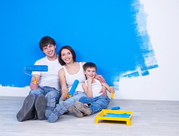 Portret van vriendelijke en gelukkige familie zittend op de vloer met penseel
