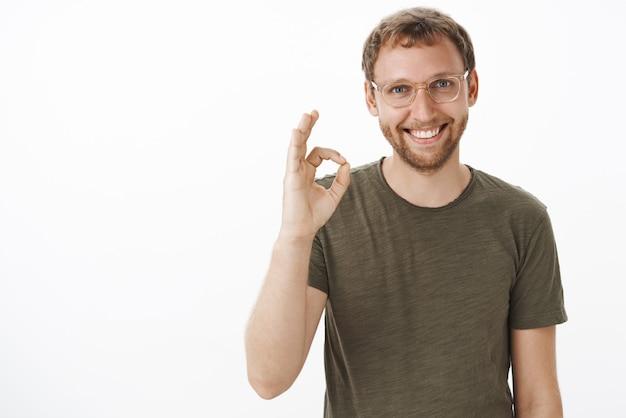 Portret van vriendelijke, knappe, behulpzame europese man in bril met baard die ok of ok gebaar toont en glimlachend verzekert dat de klantdeal wordt ondertekend