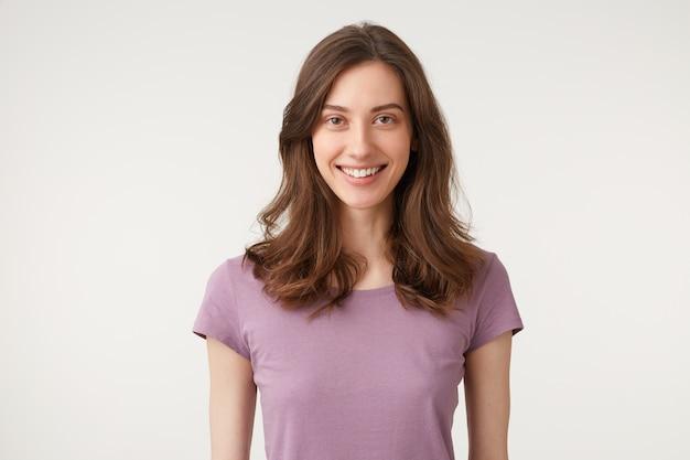 Portret van vriendelijke knappe vrouwelijke student met lang donker haar breed glimlachend en positieve houding uitdrukken