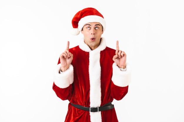 Portret van vriendelijke man 30s in kerstman kostuum en rode hoed gebaren vingers omhoog