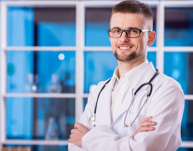 Portret van vriendelijke mannelijke arts kijkt naar de camera.