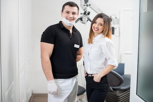 Portret van vriendelijke mannelijke tandarts met gelukkige vrouwelijke patiënt in moderne tandheelkundige kliniek