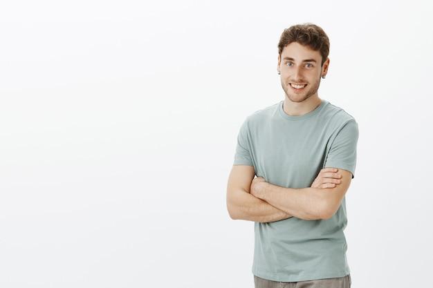 Portret van vriendelijke opgewonden knappe man met blond haar en oorbellen