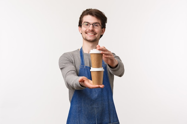 Portret van vriendelijke vrolijke jonge mannelijke werknemer in schort, werkende coffeeshop geven klant zijn bestelling twee kopjes drank, bereide cappuccino en lachend als zeggen genieten van je drankje