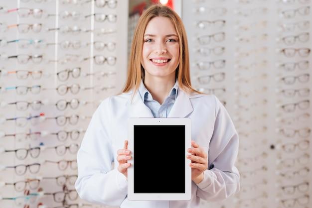 Portret van vriendelijke vrouwelijke optometrist weergegeven: tablet-sjabloon