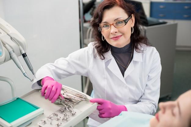Portret van vriendelijke vrouwelijke tandarts met vrouwelijke patiënt in de tandheelkundige kantoor. tandheelkunde. tandheelkundige apparatuur