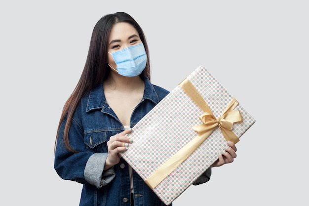 Portret van vriendelijkheid aantrekkelijke jonge aziatische vrouw met medisch masker in blauw spijkerjasje dat aanwezig is en glimlacht, kijkend naar de camera. binnen, geïsoleerd, studio-opname, grijze achtergrond